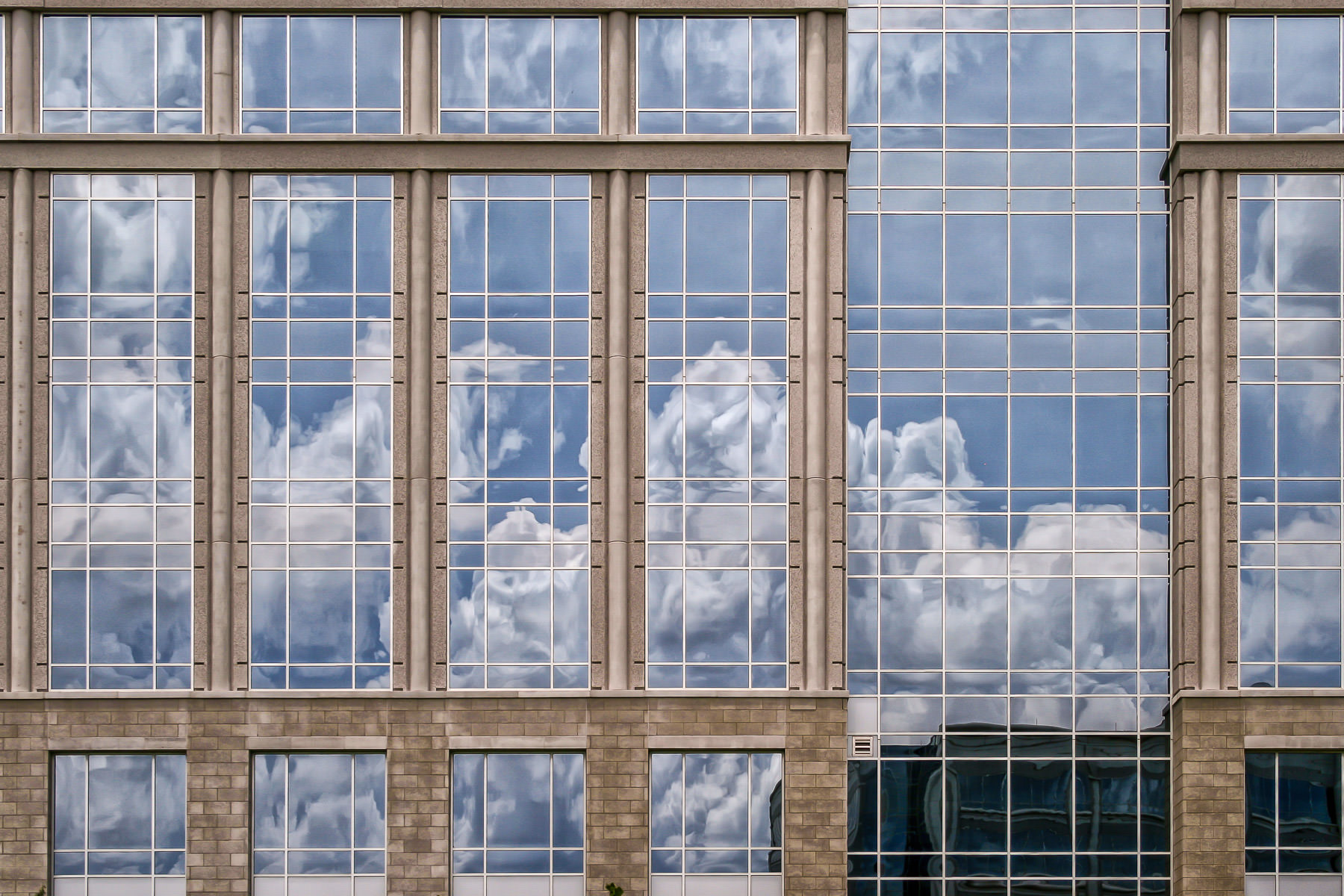 Clouds reflected in the windows of an office building in Frisco, Texas.