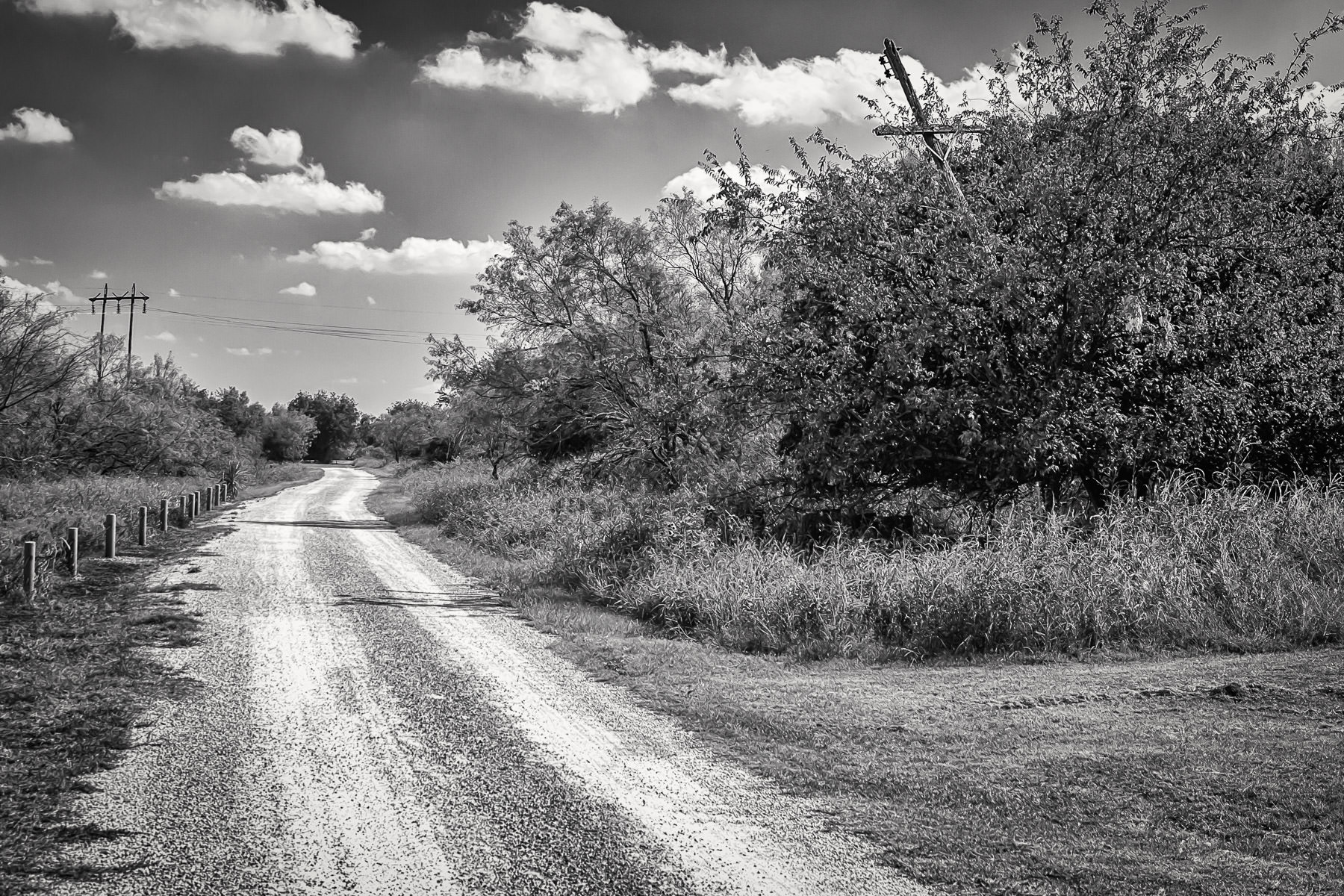 A caliche road leads through the brush a Fort Richardson State Park in Jacksboro, Texas.