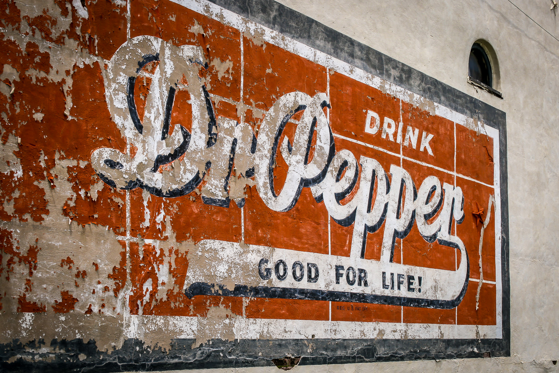 A cracked and fading Dr Pepper sign on the side of a decaying building in Downtown Pilot Point, Texas.