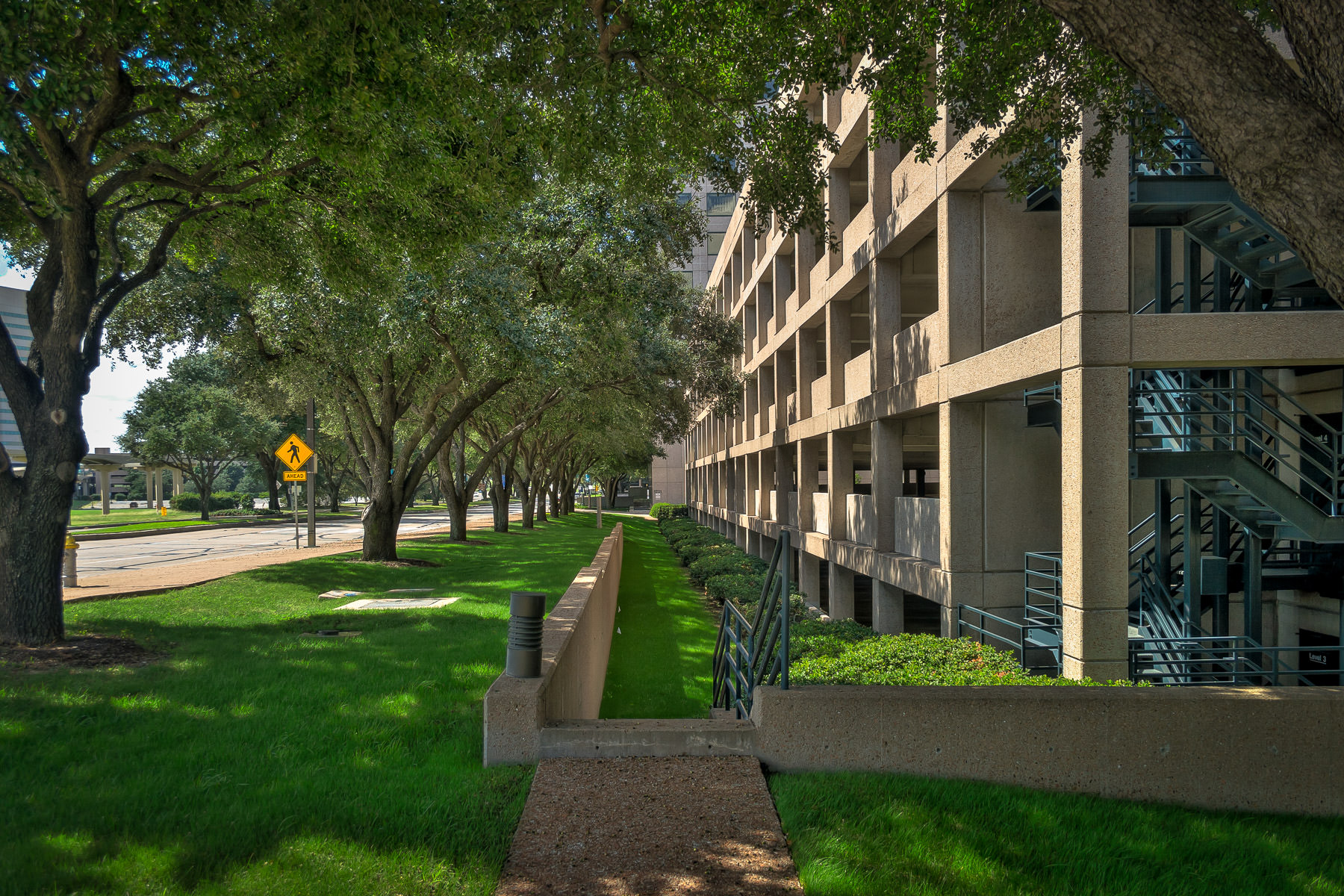 A stairway that seems to lead to nowhere between a tree-lined street and an office block in Las Colinas, Irving, Texas.