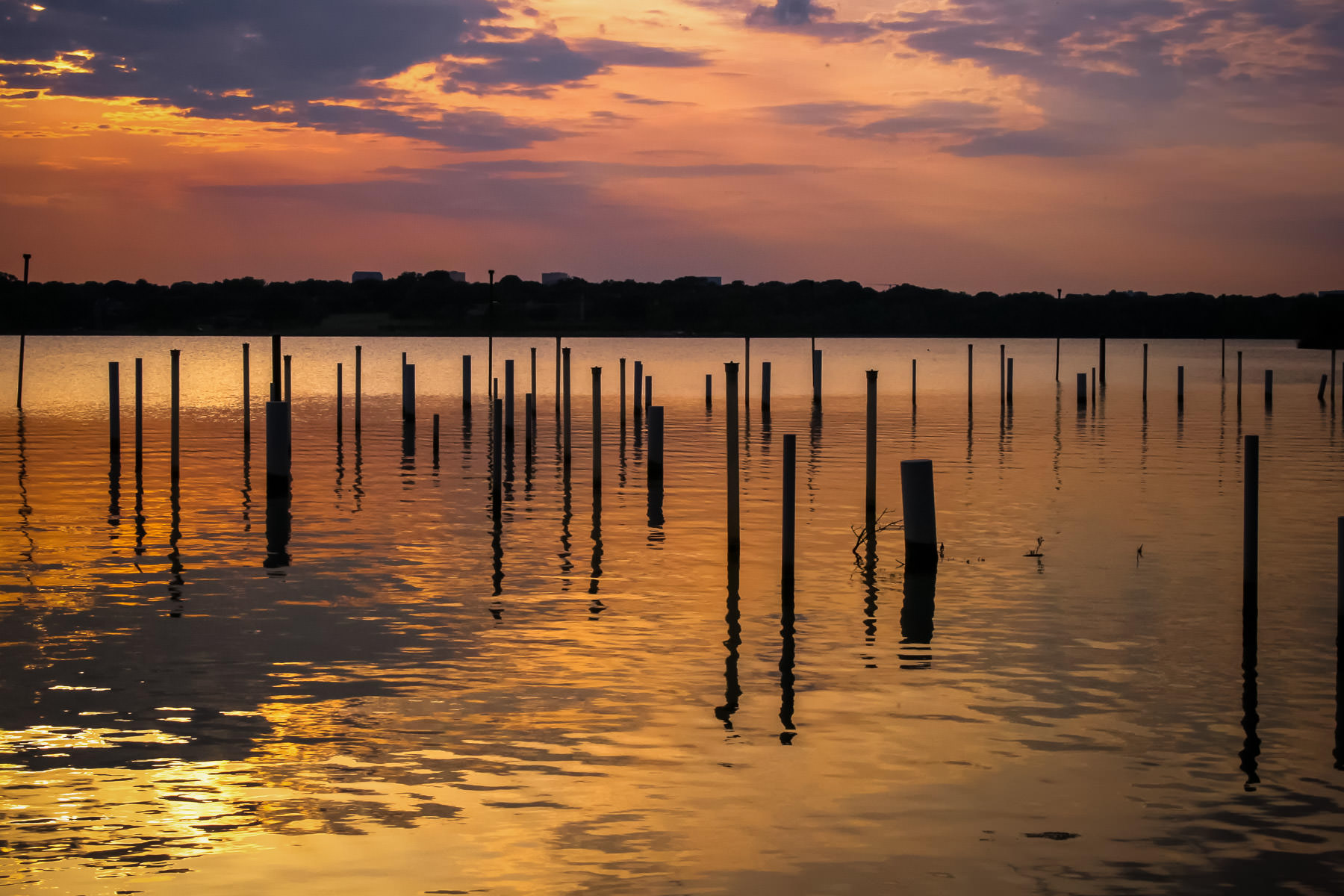 "The sun sets over Dallas' White Rock Lake. The poles in the foreground are part of an art installation by Frances Bagley and Tom Orr entitled ""Water Theater""."