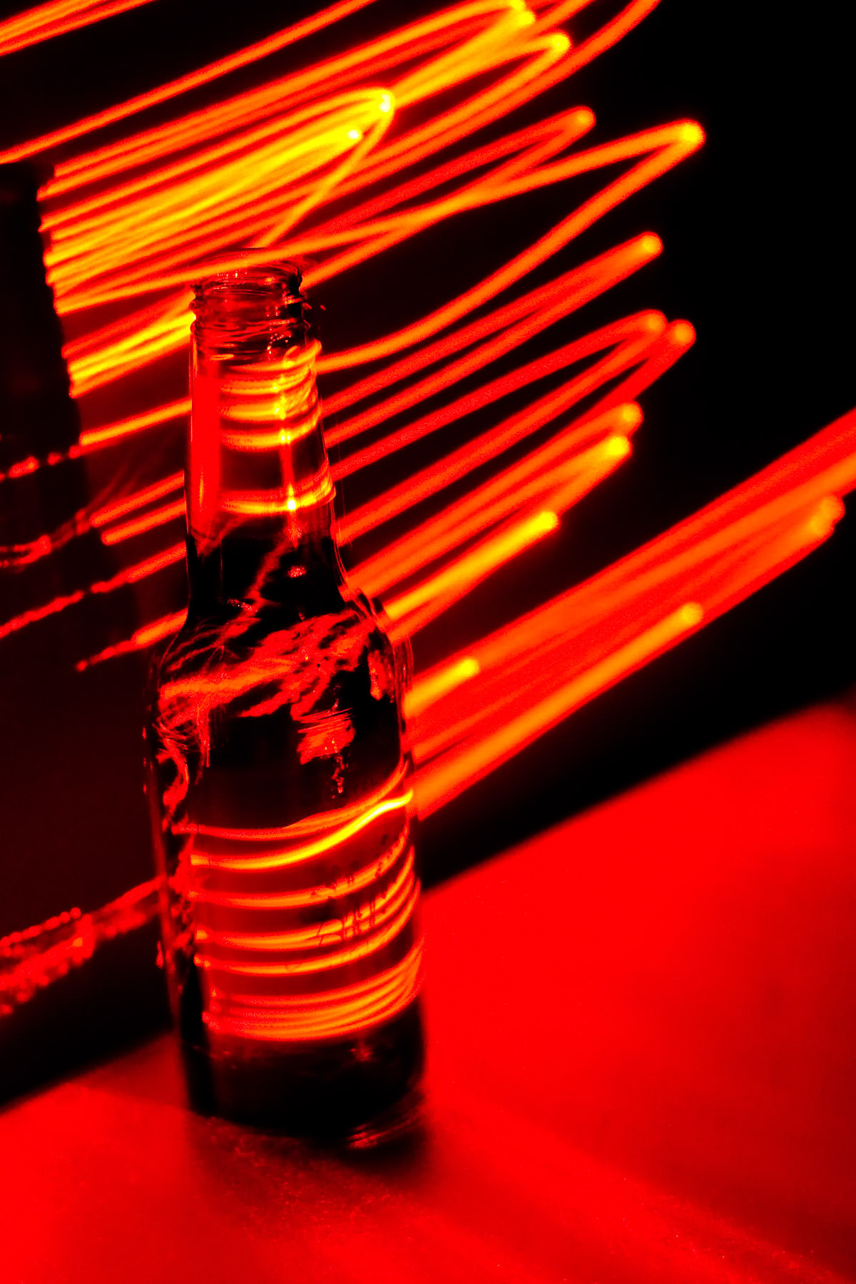 A Shiner Bock beer bottle illuminated by a laser pointer in a long-exposure shot.