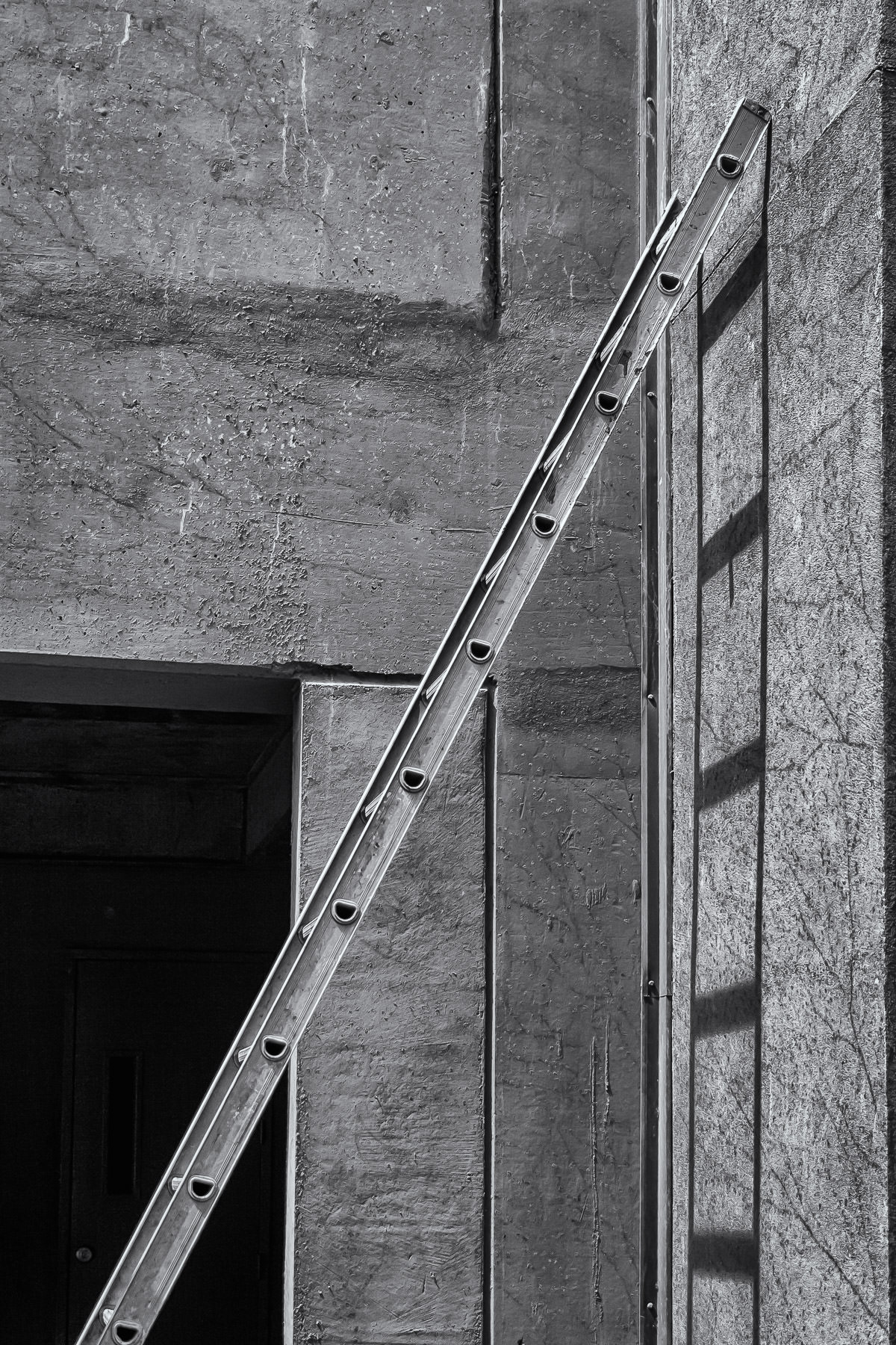 A ladder leaning unattended against a wall in Downtown Plano, Texas.