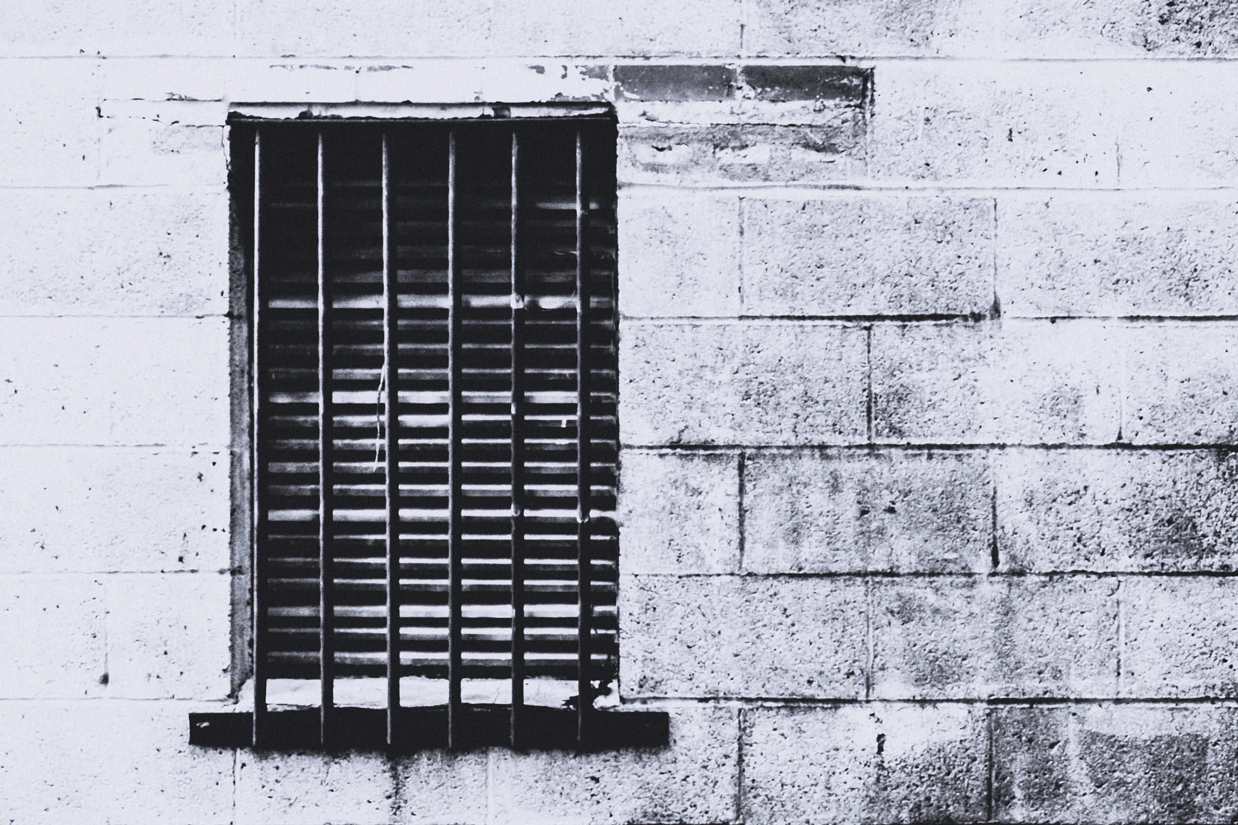 A window with bars over it in a back alley in Corsicana, Texas.