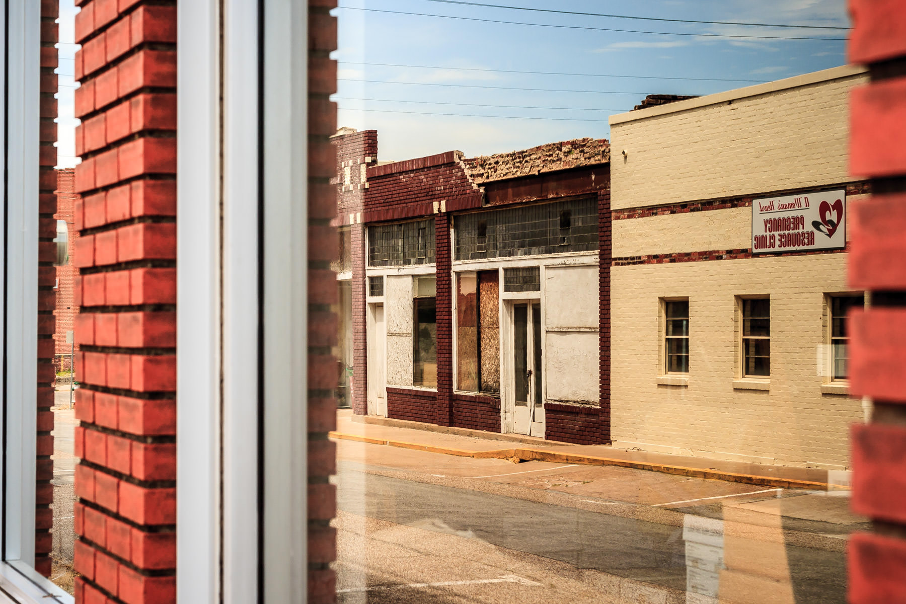 Windows reflect the street in Downtown Greenville, Texas.