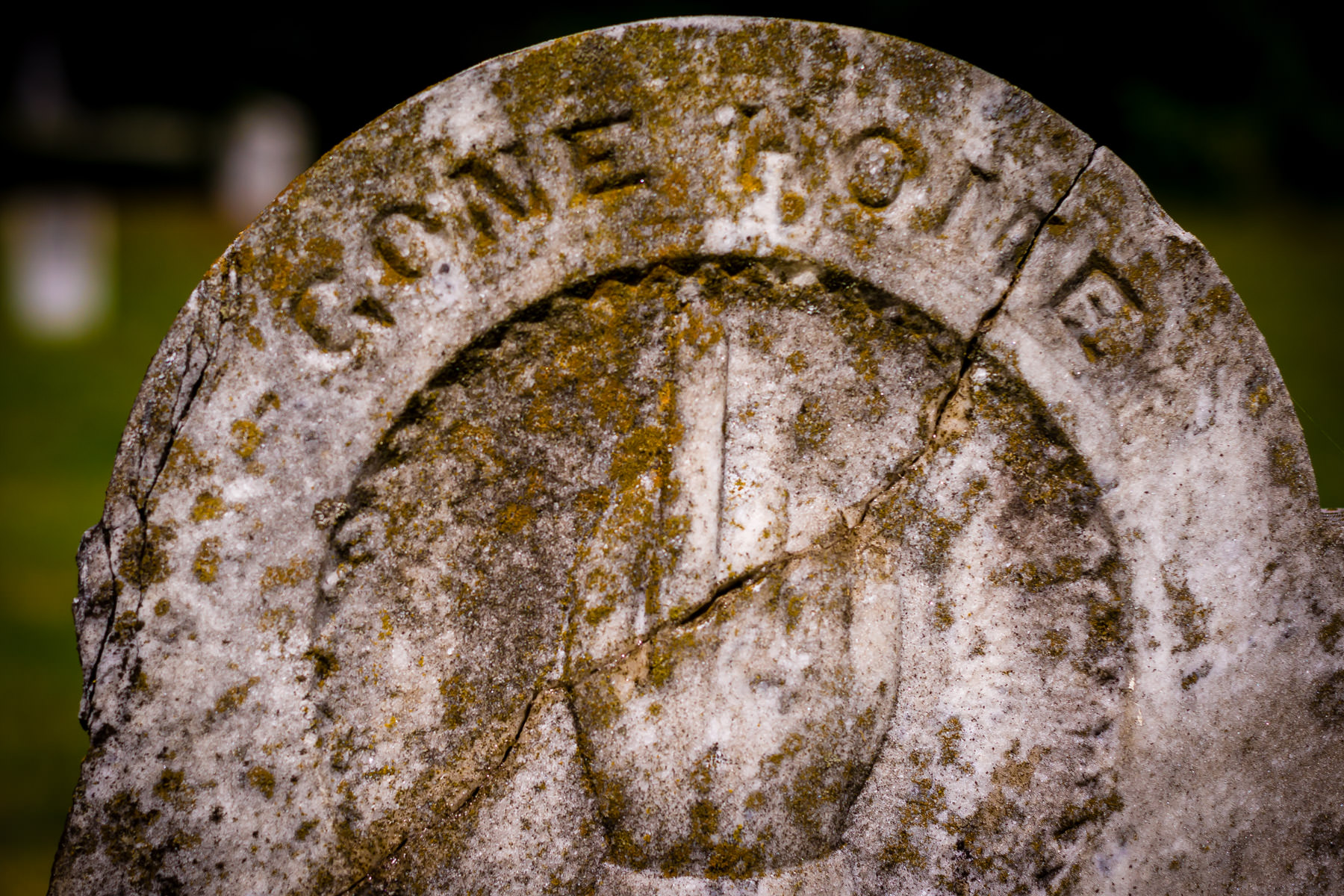 Detail of a crumbling, moss-covered grave stone at Minter's Chapel Cemetery on the grounds of DFW International Airport, Texas.