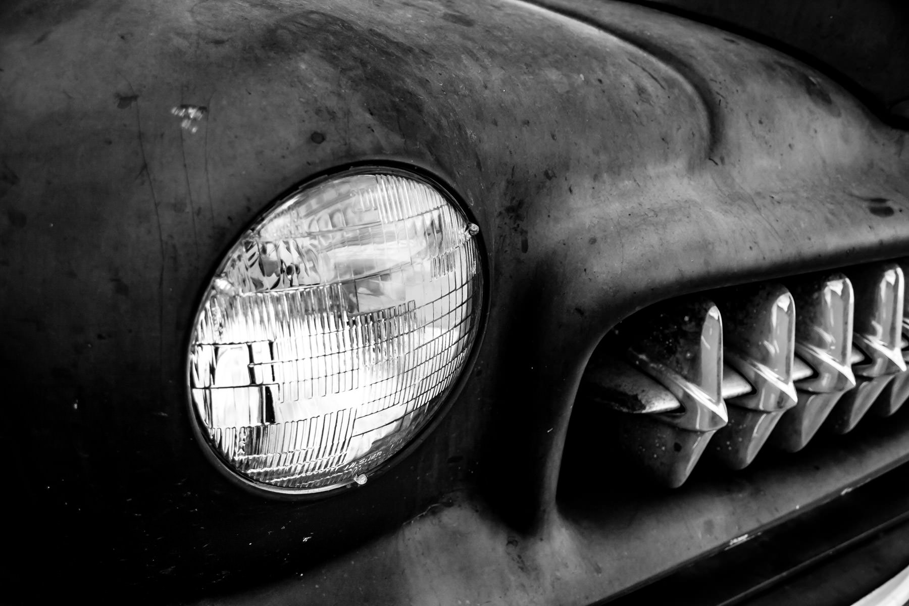 The headlight of a broke-down, abandoned classic Mercury found atop the parking garage of Eastside Village in Downtown Plano, TX.
