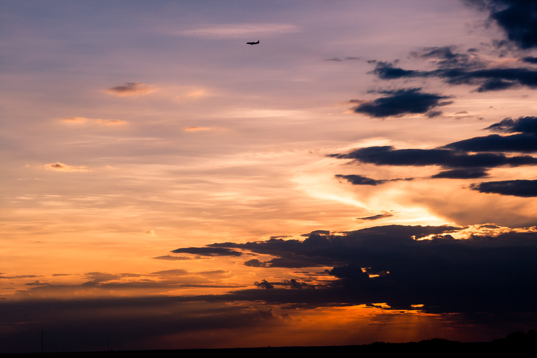 A jet on approach to DFW International Airport as the sun sets on Far North Dallas, Texas.