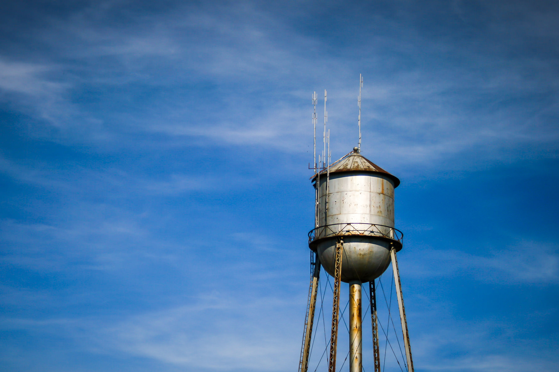 A water tower rises into the blue sky of Overton, Texas.
