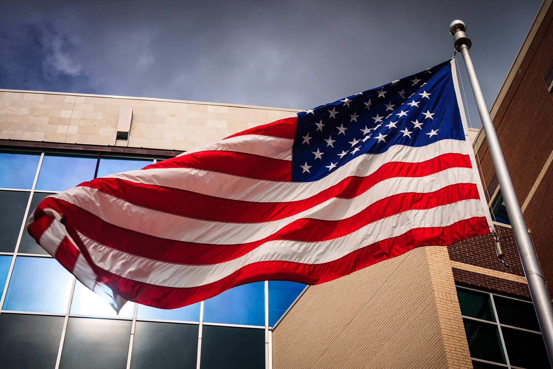 An American flag waves in the wind outside the Dallas Police Department Headquarters in The Cedars, Dallas, Texas.