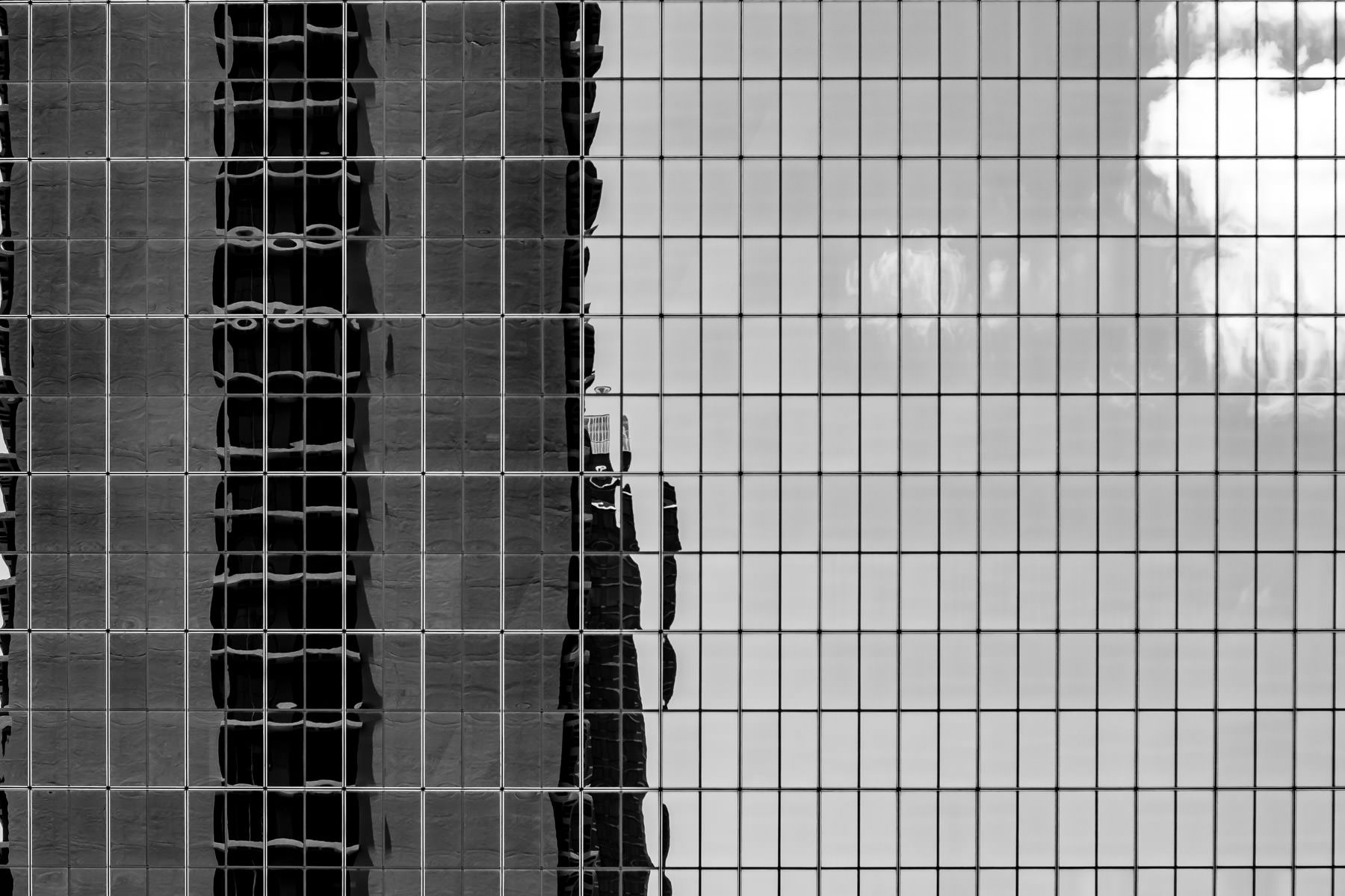 One of the towers of Downtown Dallas' Fairmont Hotel reflects in the mirror-like windows of an adjacent building.