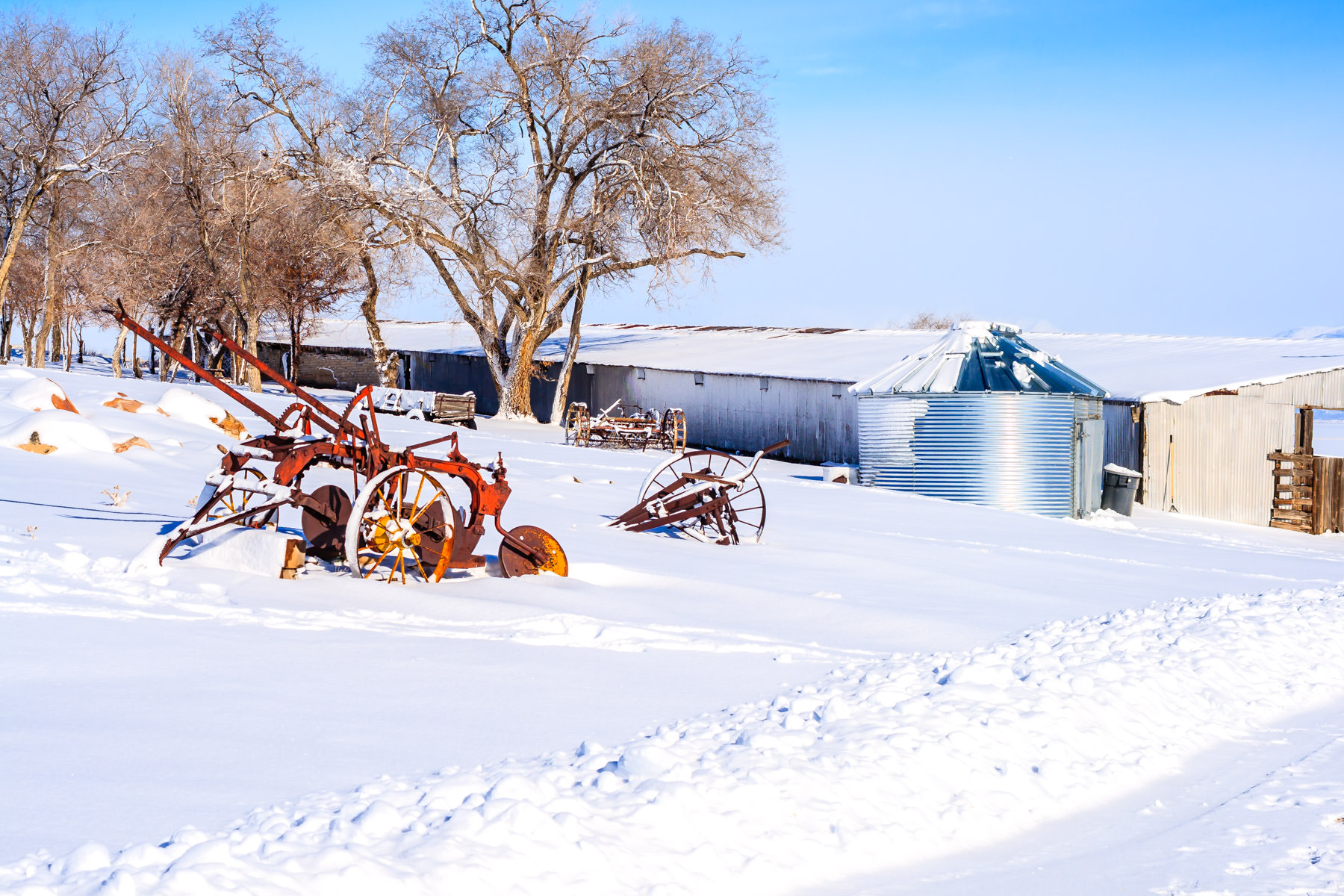 Rusting farm equipment lies in the winter snow at the Fielding Garr Ranch, Antelope Island State Park, Utah.