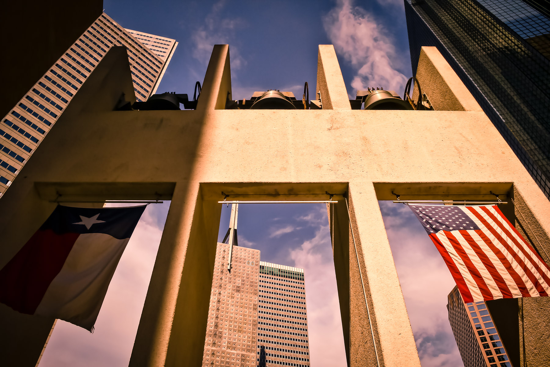 Texas and United States flags hang from a small carillon in Dallas' Thanks-Giving Square.