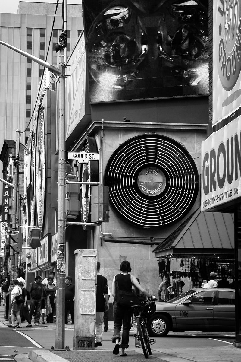 A girl walks her bike along Toronto's Yonge Street towards iconic retailer Sam the Record Man in this shot from 2004. Sadly, the store closed forever in 2007.