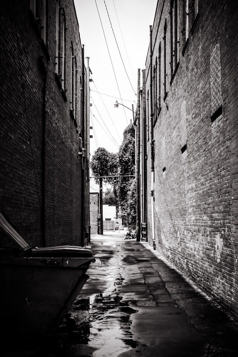 An alley leads between two buildings in Downtown Waxahachie, Texas.