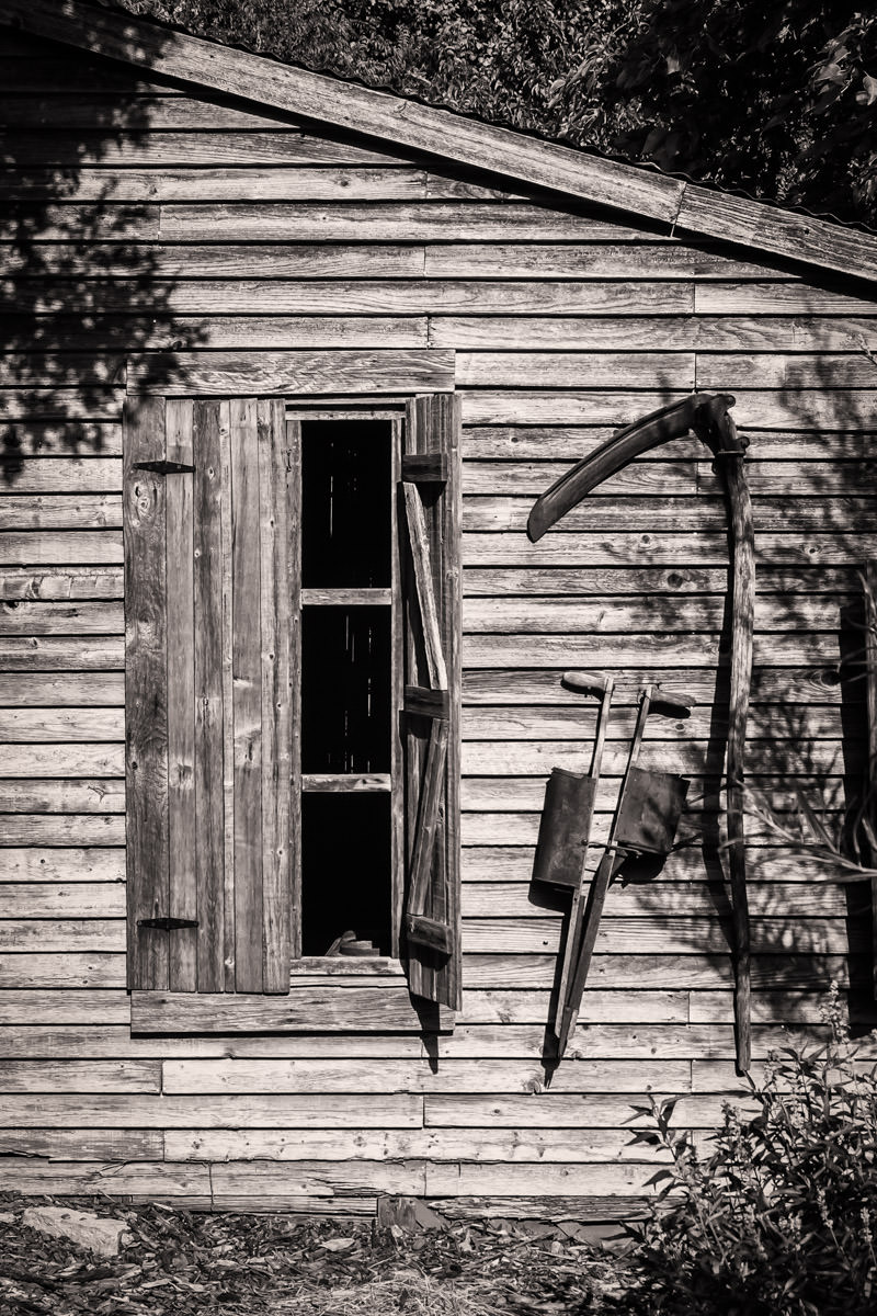 A small barn hung with farm implements at the Dallas Arboretum.