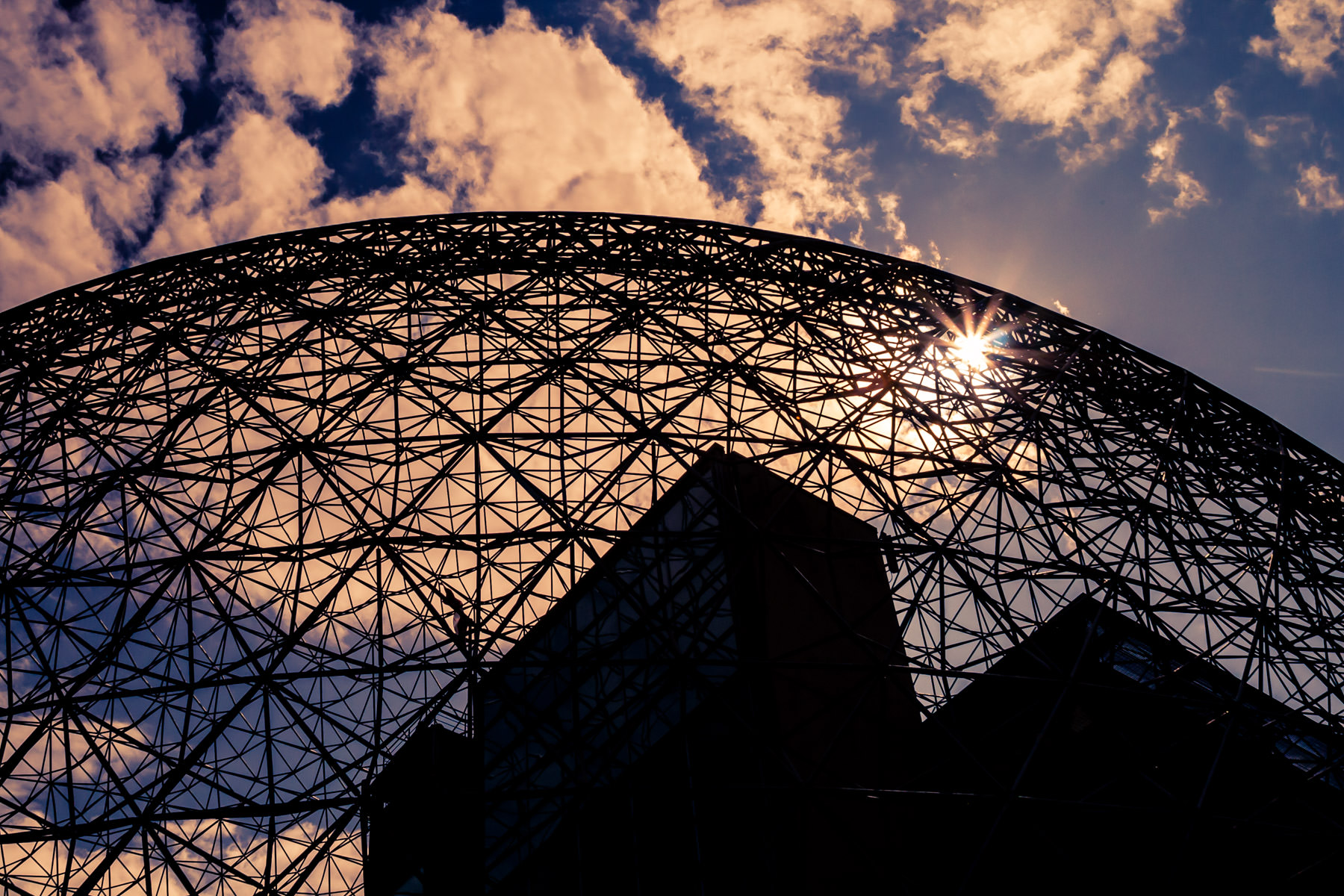 The sun peeks through the clouds above Montréal's Biosphére, the re-purposed Buckminster Fuller-designed Expo '67 United States Pavilion.