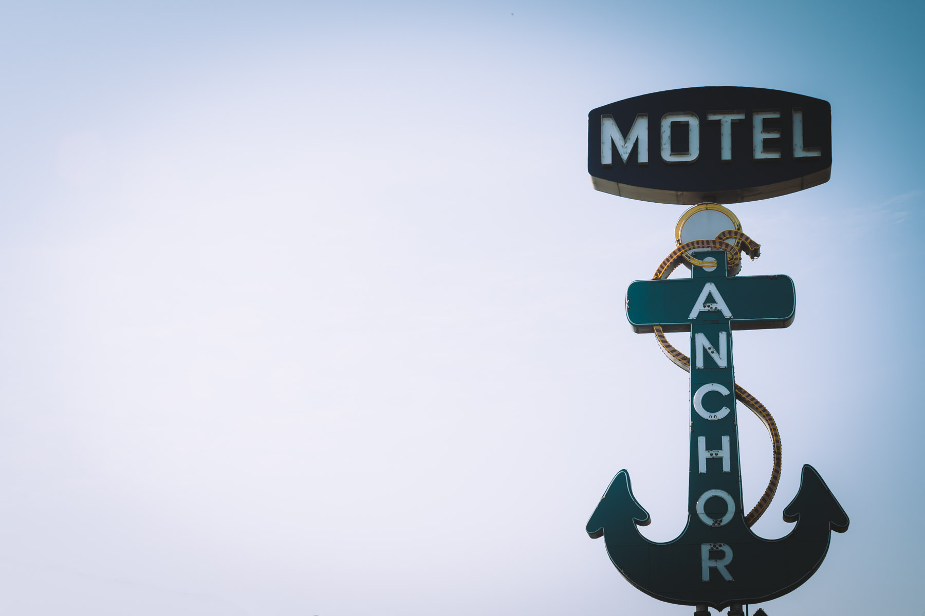 The sign for Dallas' Anchor Motel rises into the early-morning sky.