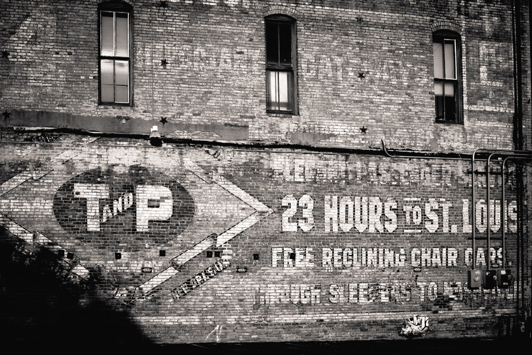A faded Texas & Pacific Railway sign on the side of a building in Dallas' Deep Ellum neighborhood.