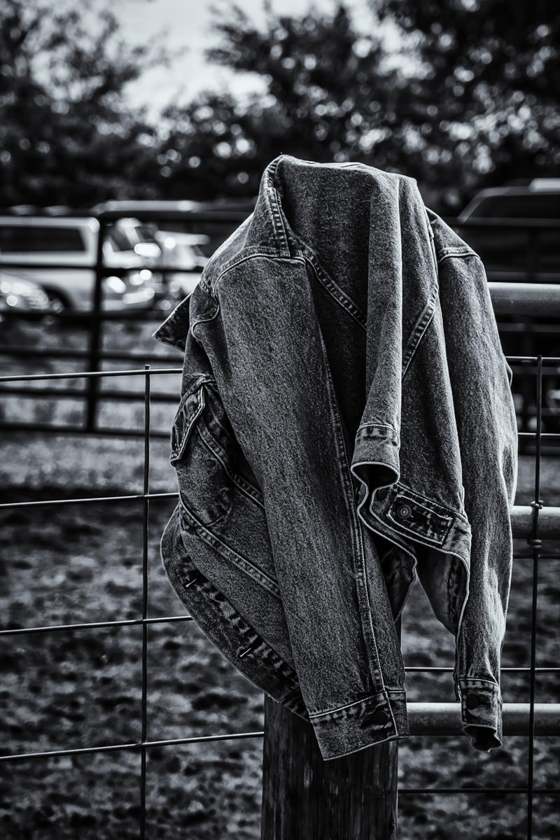 A denim jacket hangs on a fence at Moore Farms in Bullard, Texas.