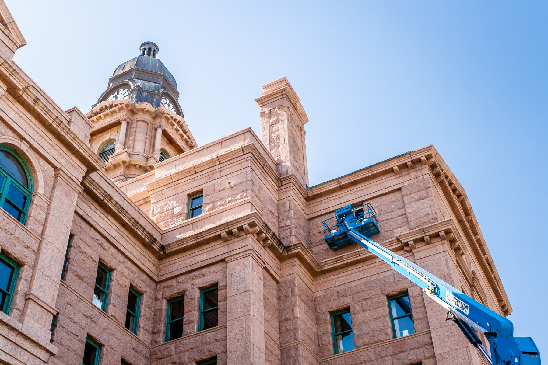 A boom lift reaches up the exterior of the Tarrant County Courthouse, Fort Worth, Texas.