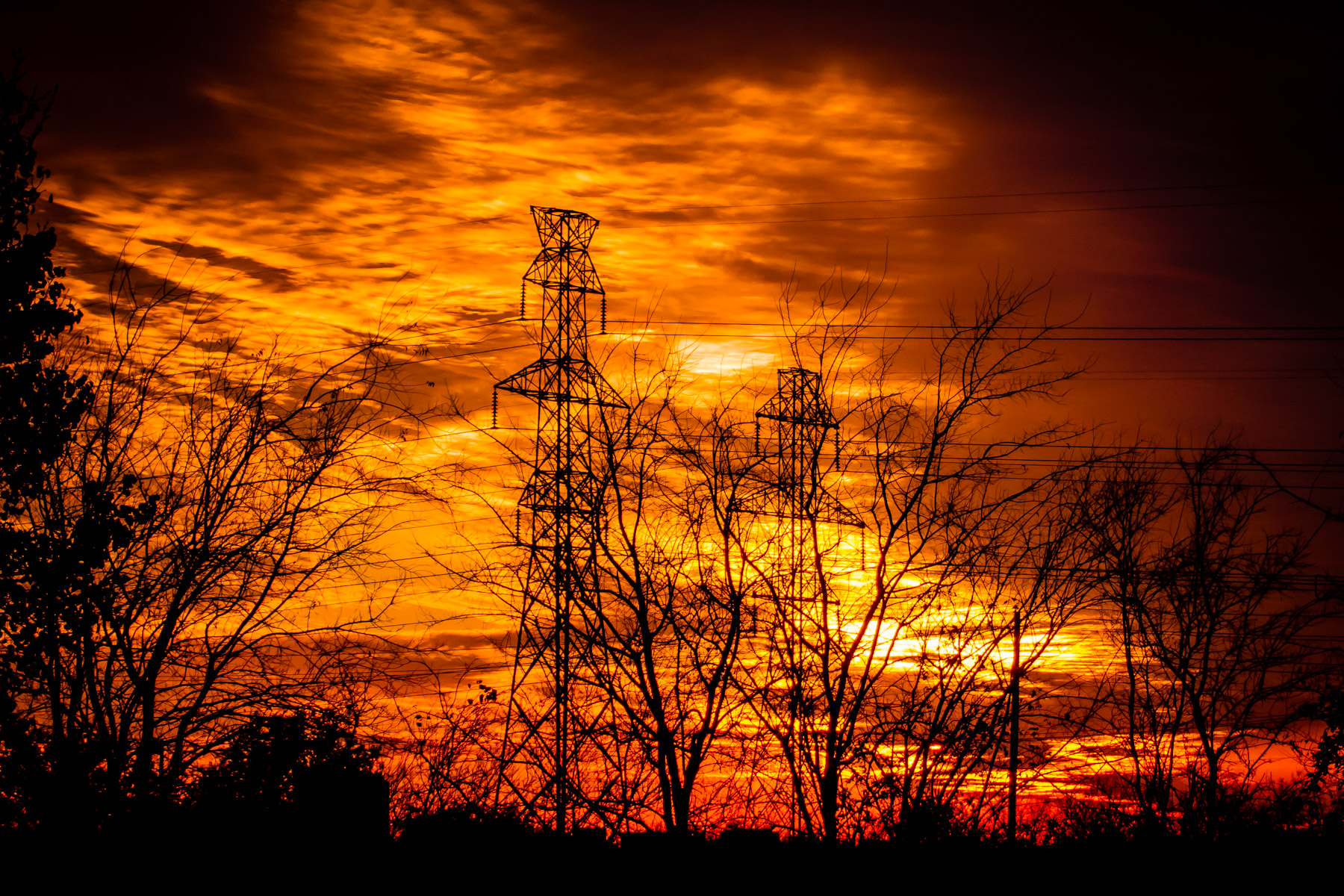 The sun sets behind electric towers in Far North Dallas.