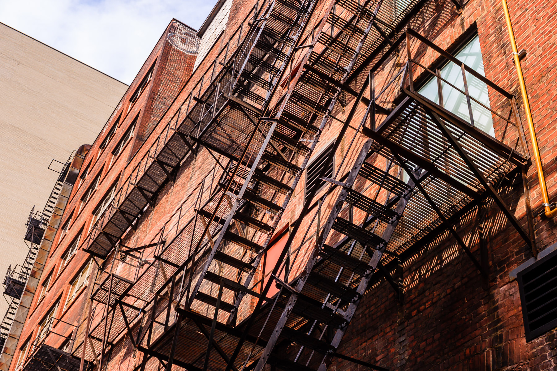 A fire escape climbs up the side of a building in Centre-ville Montréal.