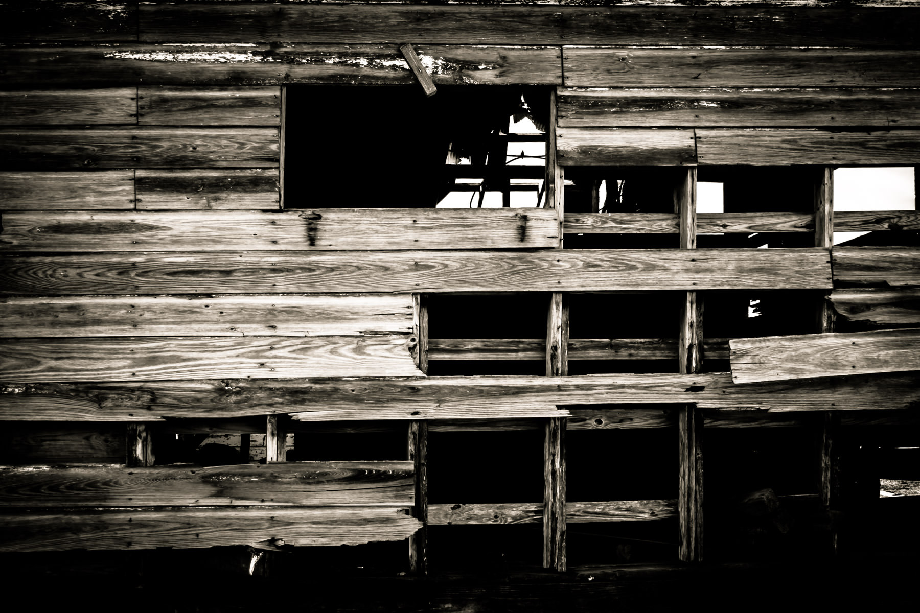 A barn's wooden wall decays in the sun of Allen, Texas.