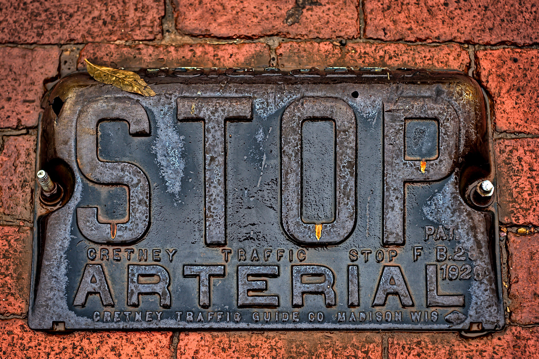 A stop sign marker embedded in the brick streets of Jefferson, Texas.