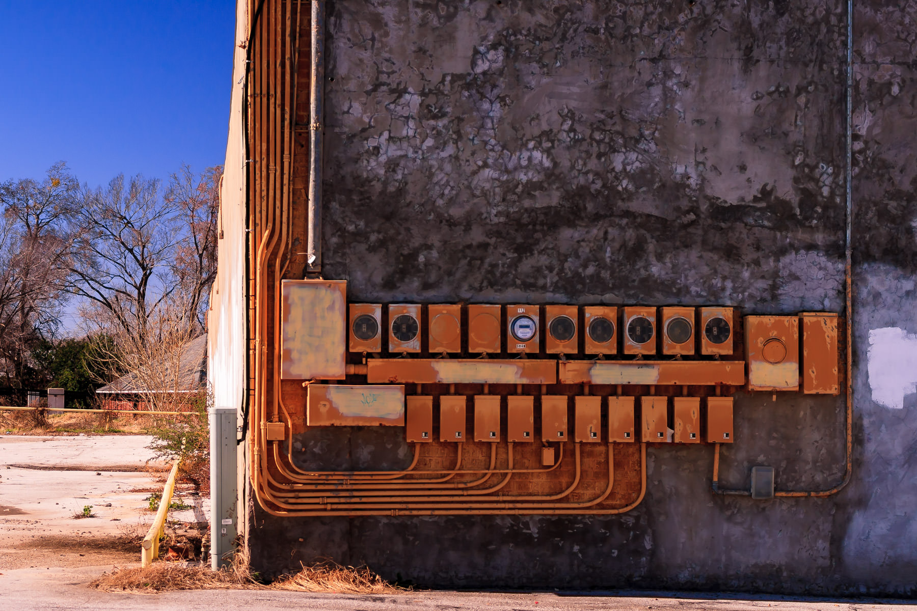 Electric meters decay on the side of an abandoned building in Tyler, Texas.