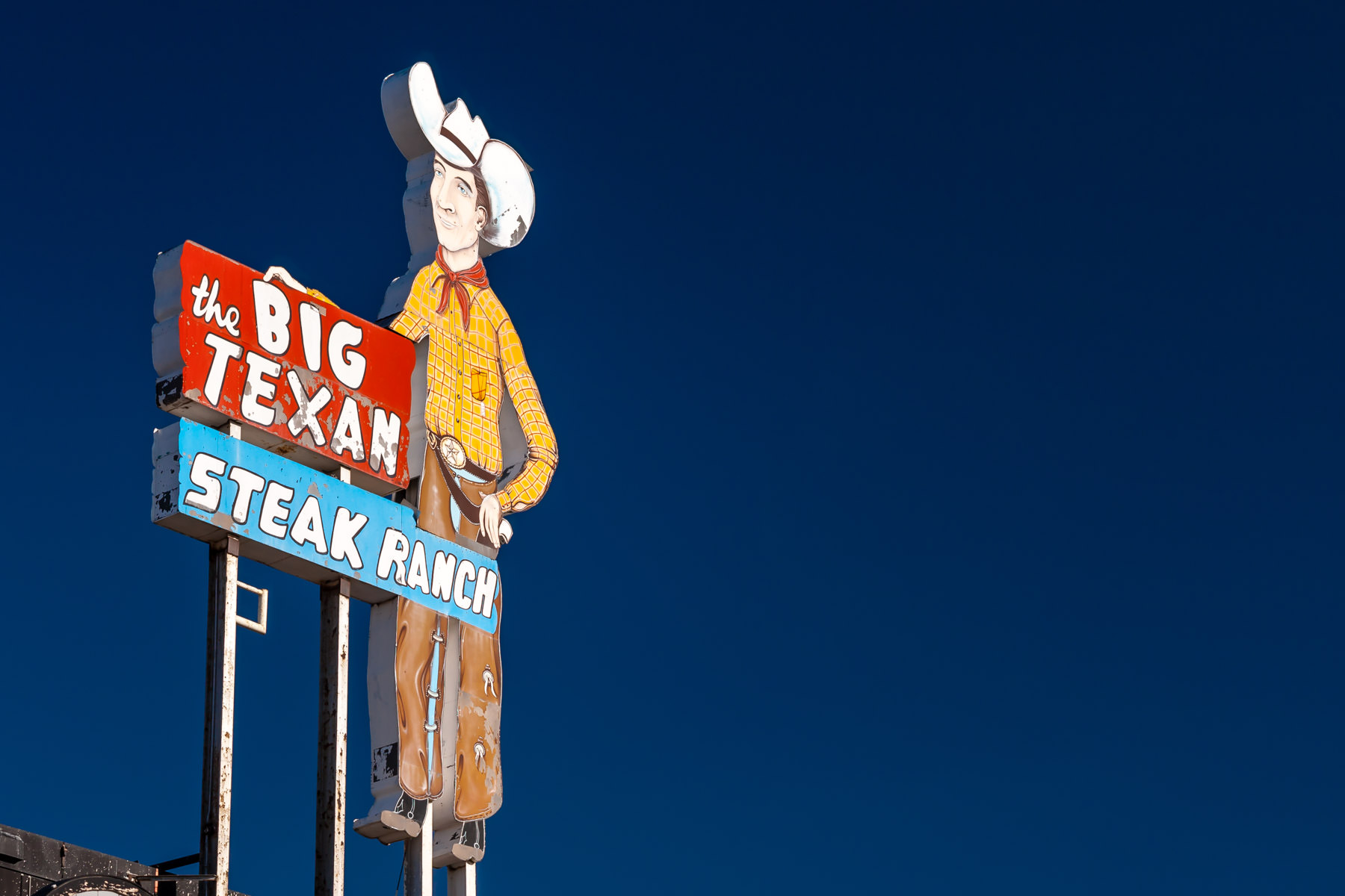 The sign of Amarillo, Texas' legendary Big Texan Steak Ranch rises into the clear, blue sky of the Texas Panhandle.