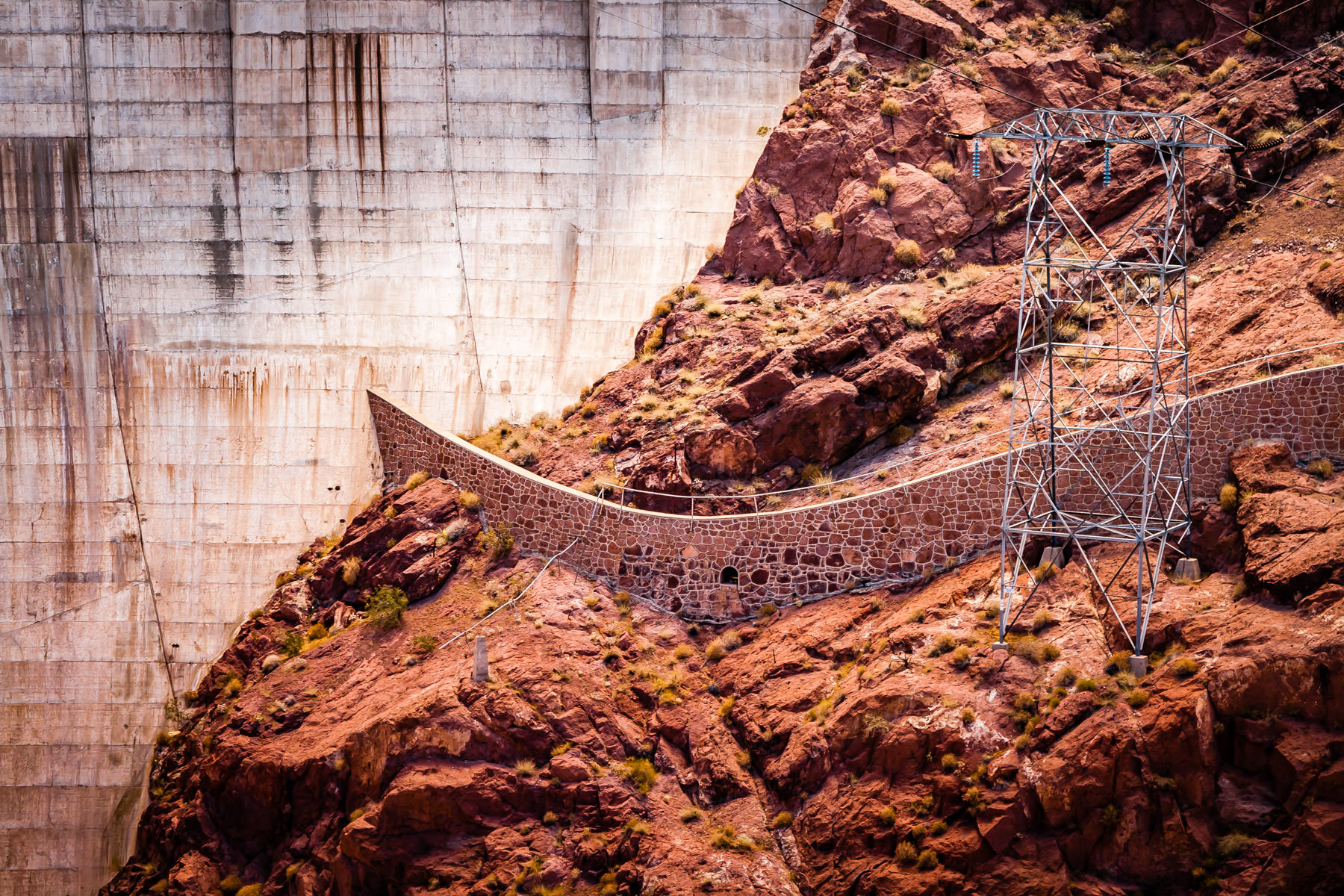 A rock retaining wall and electrical tower next to downstream face of Hoover Dam.