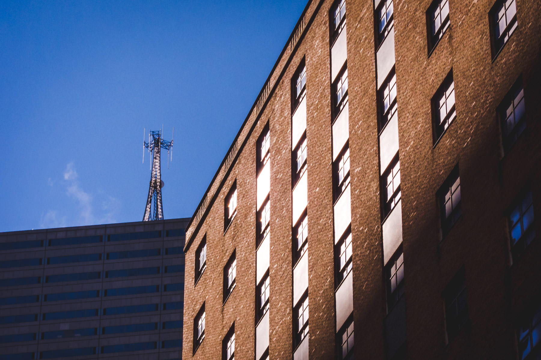 An uniquely-designed antenna tower peaks over the roof of Downtown Dallas' Energy Plaza.