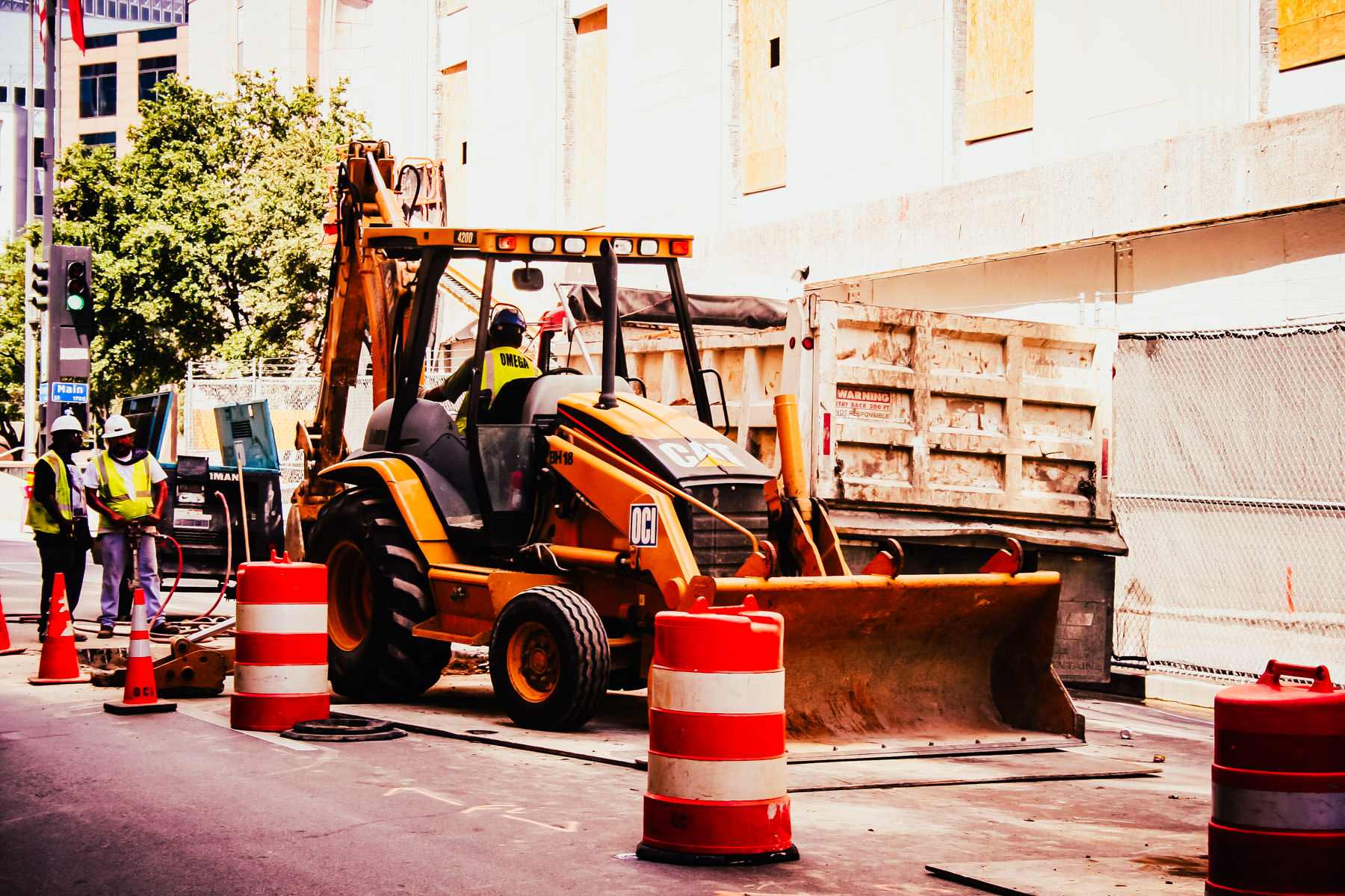 A backhoe performs Infrastructure repair on the streets of Downtown Dallas.