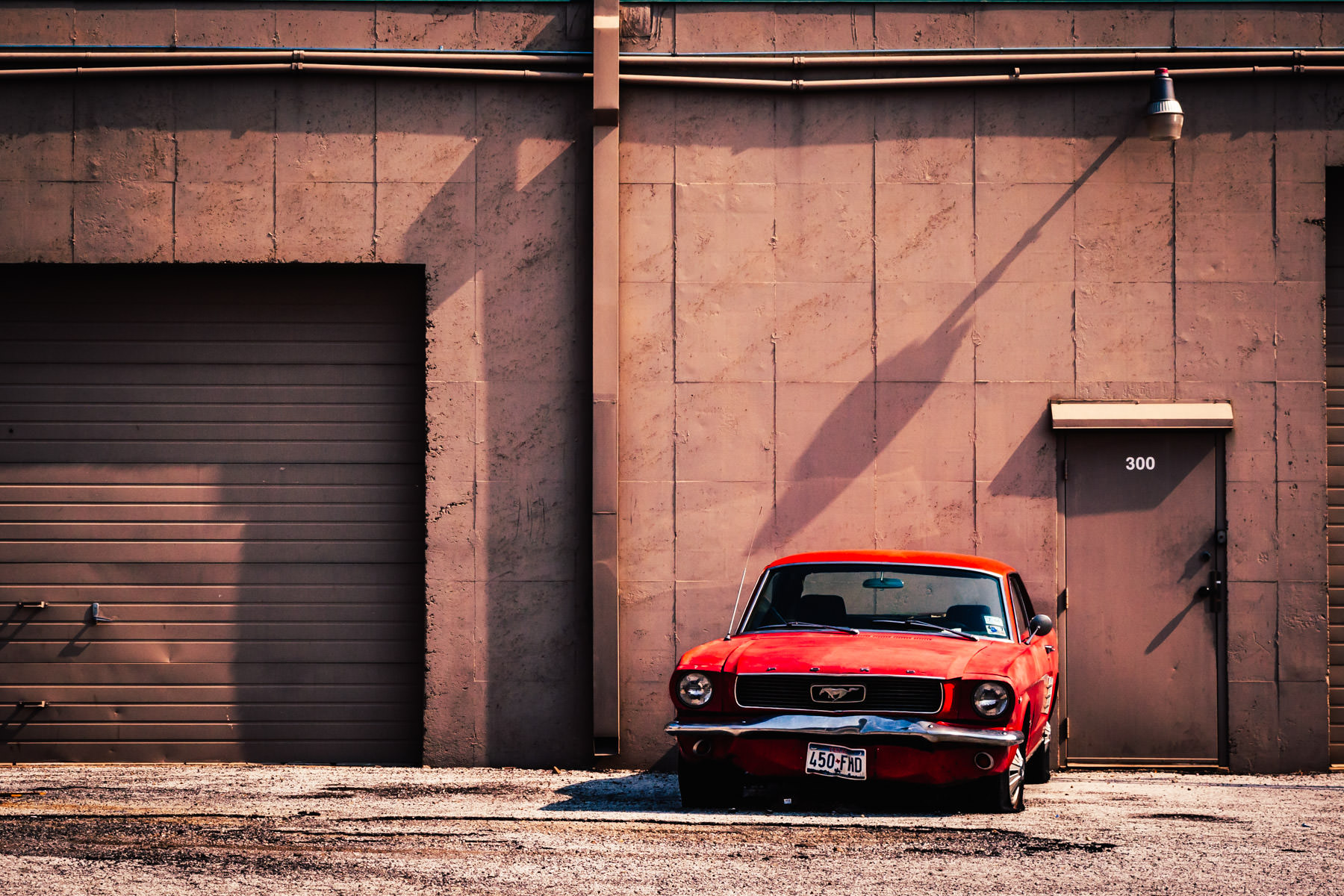 A broken-down Ford Mustang behind a warehouse in Addison, Texas.