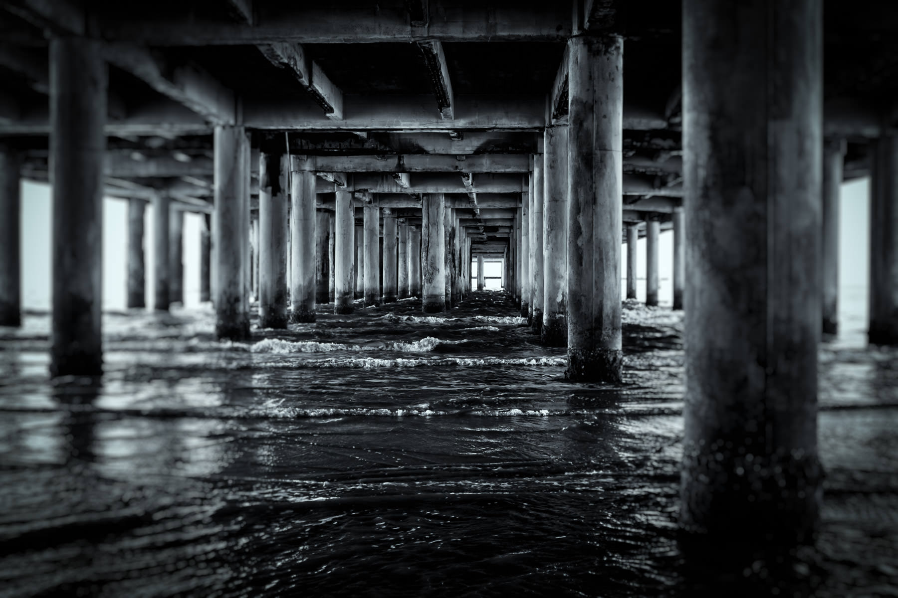 Surf of the Gulf of Mexico laps at pilings under the decaying Flagship Hotel, Galveston, Texas.