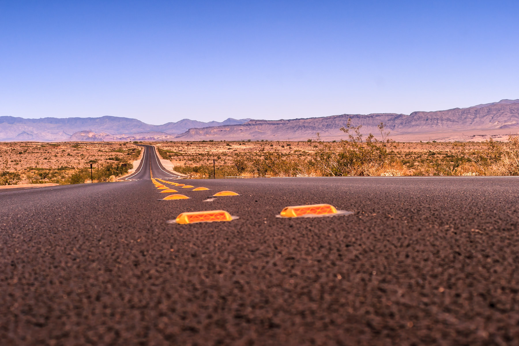 A lonesome road leading to the desert mountains somewhere in Nevada east of Las Vegas near the Arizona border.