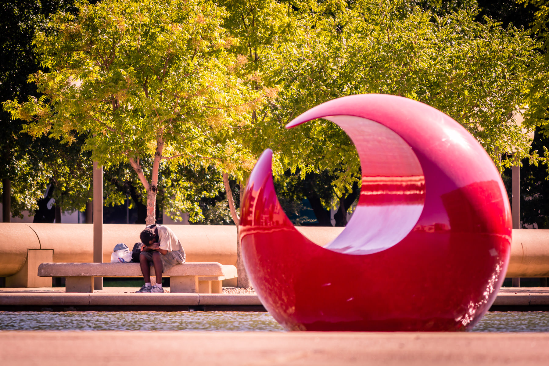 A homeless person seeks respite from the Texas sun while artist Marta Pan's Floating Sculpture reflects the cityscape in front of Dallas City Hall.