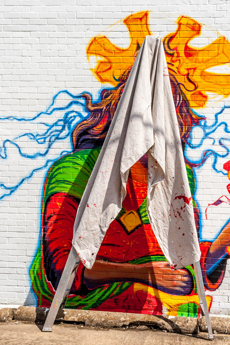 A painter's drop cloth draped over a ladder obscures a mural of Jesus Christ on the outside of a shop, Oak Cliff, Dallas.