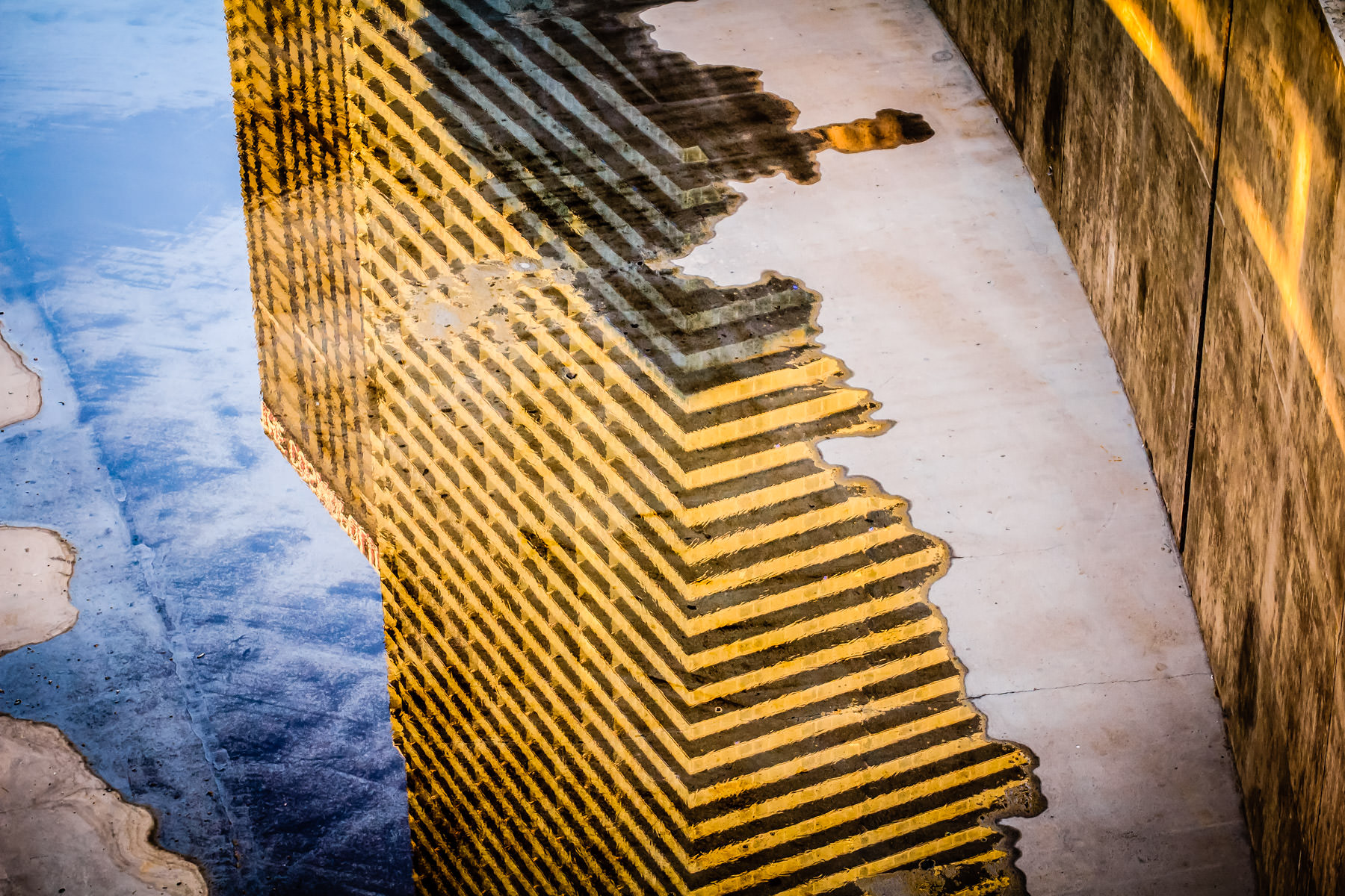 The Cosmopolitan of Las Vegas, reflected in a nearby puddle as the sun rises over the Las Vegas Valley.