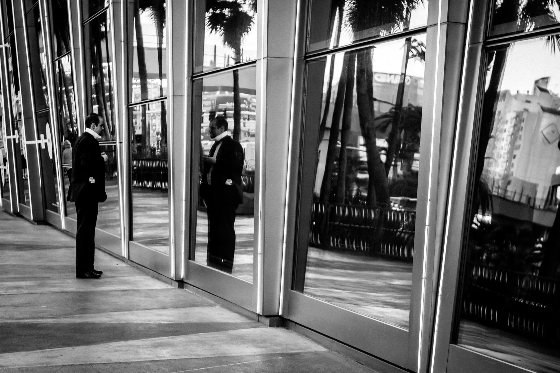 Pausing to use windows as a mirror to tie his necktie, this subject was spotted in front of the Cosmopolitan of Las Vegas.