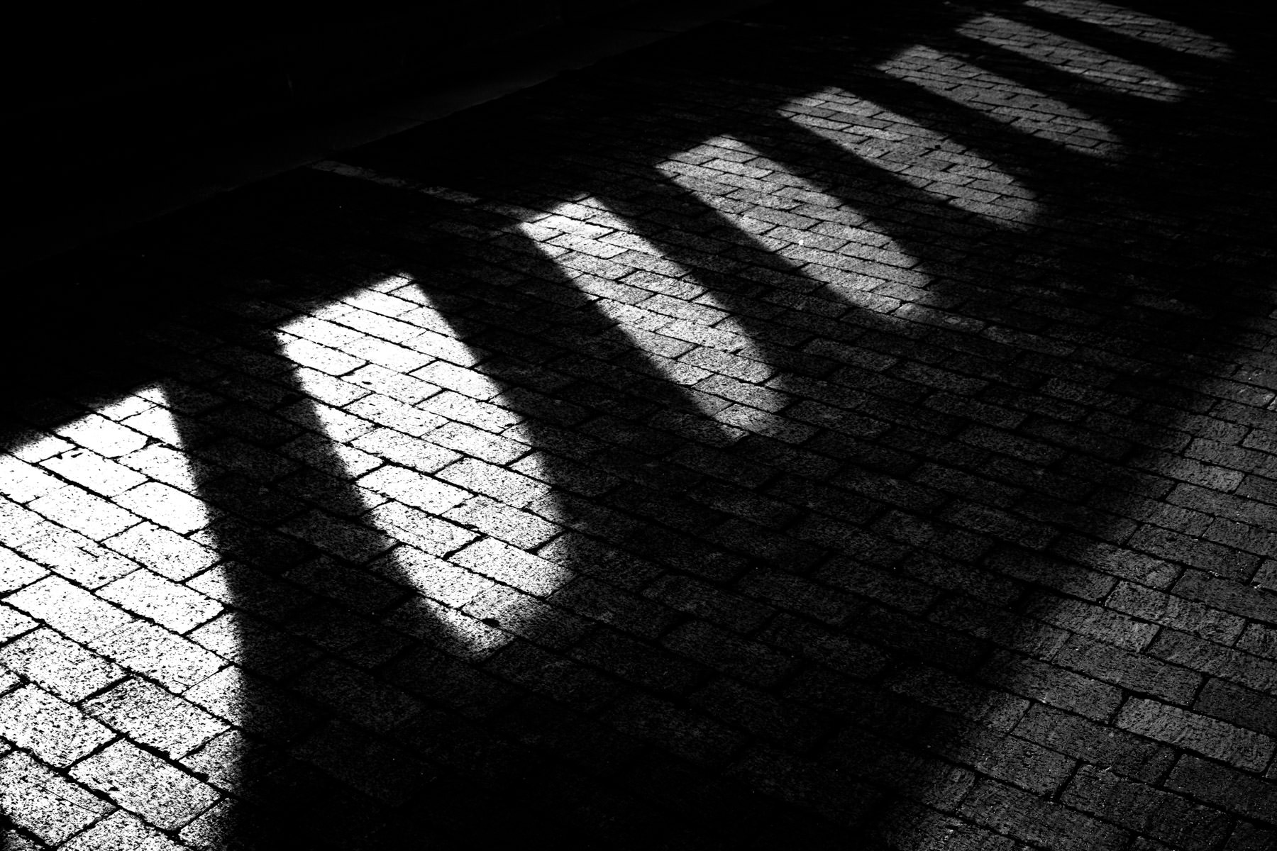 An old bridge's concrete railing casts a shadow on a brick street in Fort Worth, Texas.