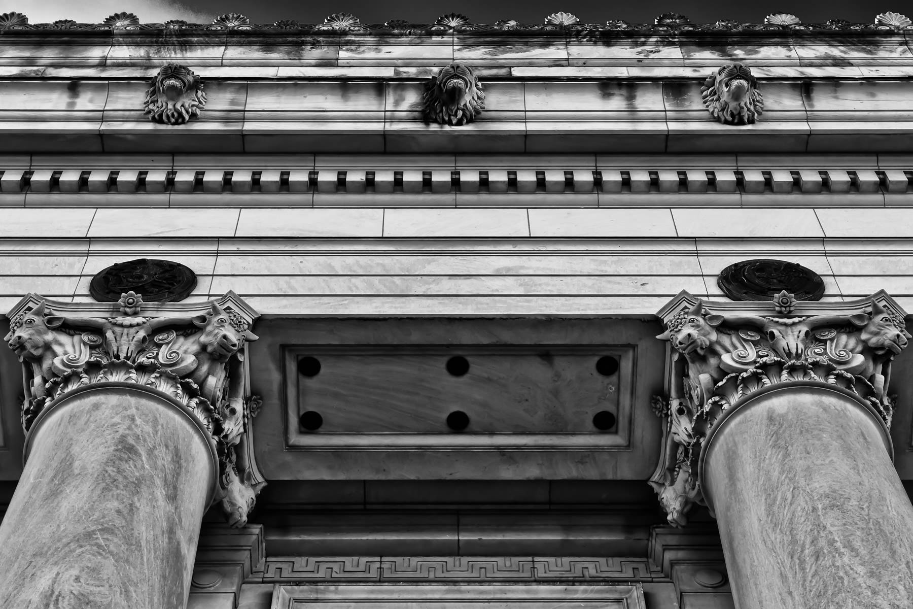 Exterior detail of the main post office in Fort Worth Texas, featuring lion heads along the frieze and various cow heads at the tops of the columns.
