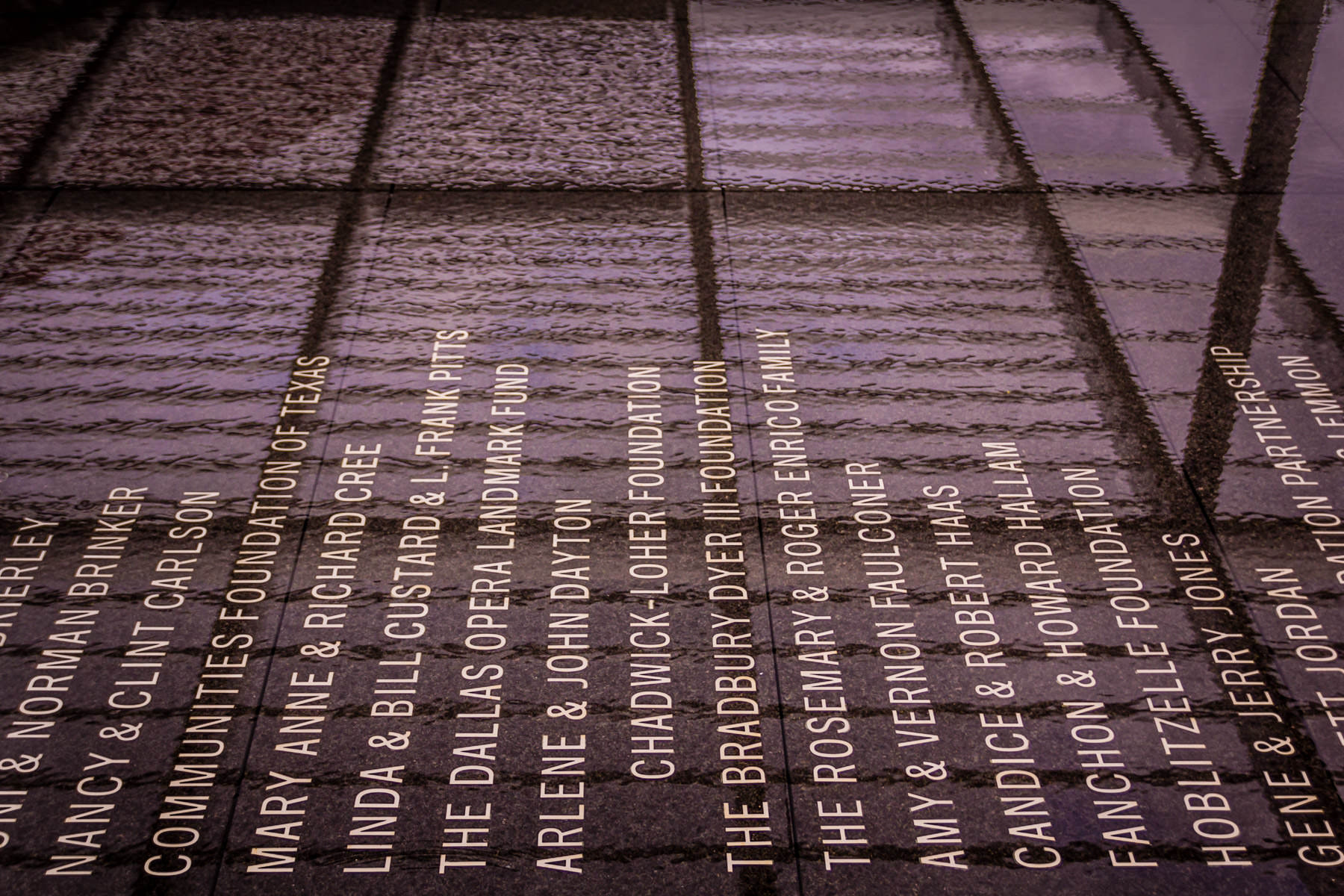Names of donors carved into the granite bottom of a reflecting pool outside of Dallas' Winspear Opera House.