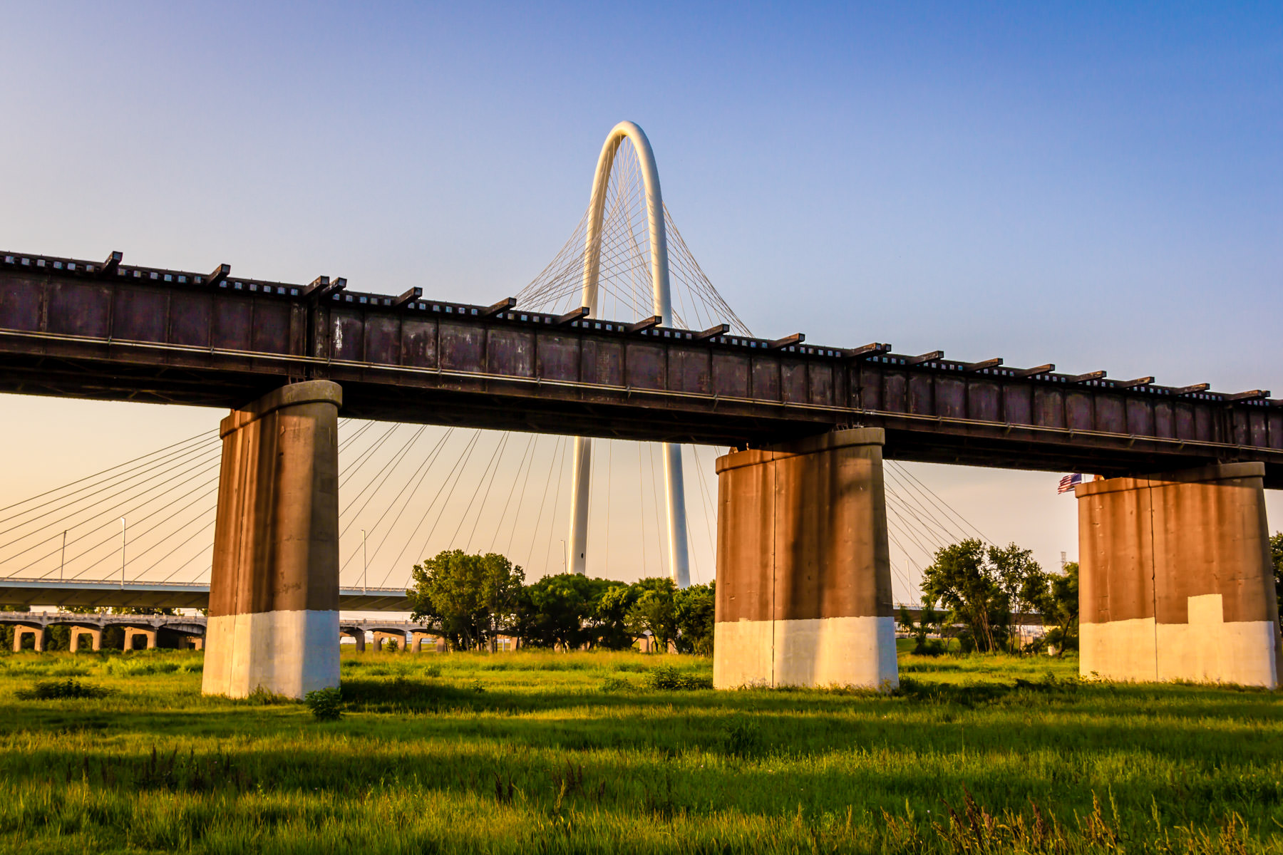 A railroad bridge, in the foreground, is overwhelmed by the massive arch and cables of Dallas' Margaret Hunt Hill Bridge as the sun sets over the DFW Metroplex.