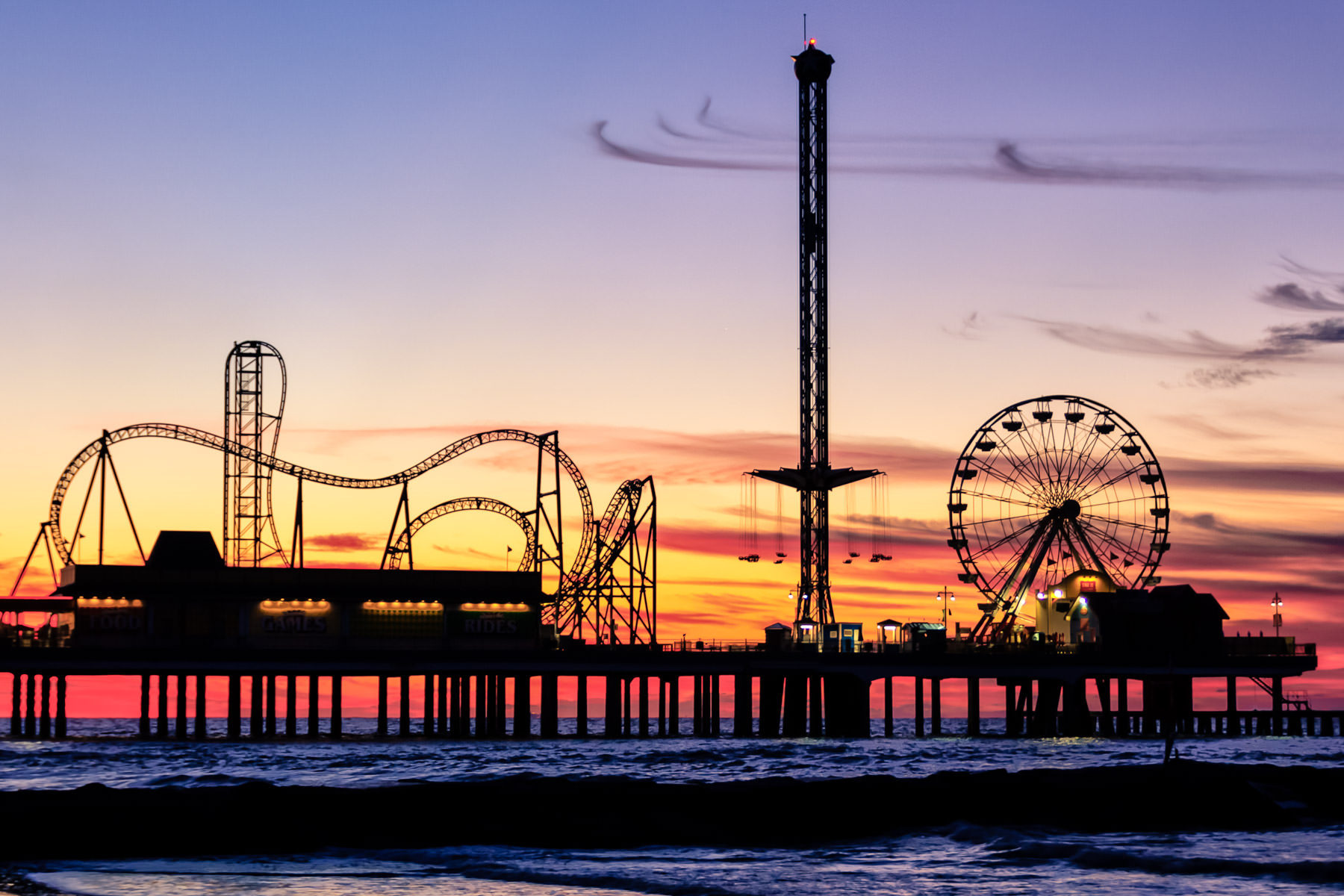 Galveston, Texas' Historic Pleasure Pier, silhouetted by the sunrise.