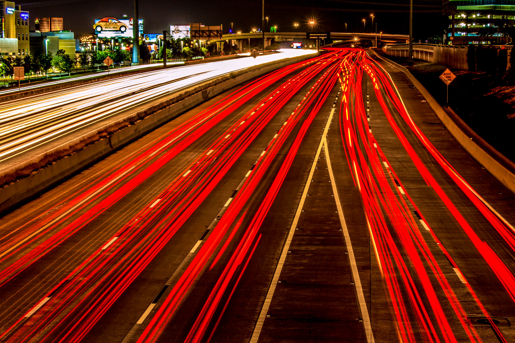 Cars exiting from Dallas' eastbound I-635 merge with the southbound lanes of US 75 in this long exposure shot taken from a bridge over the roadway.