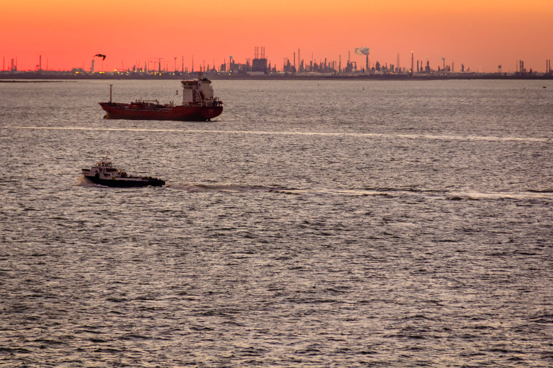 The sun sets behind the refineries of Texas City on the shoreline of Galveston Bay.
