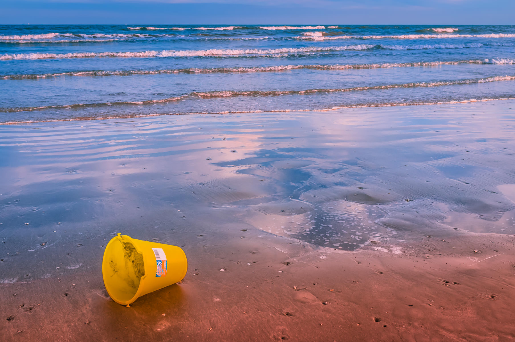 A lonely sand bucket on the Galveston Island, Texas beach.