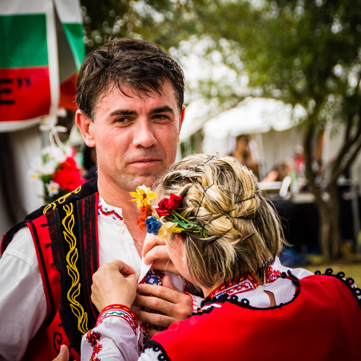 A Bulgarian dancer's traditional costume is adjusted by his companion at Addison Worldfest, Addison, Texas.